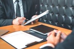 Le cadre supérieur lisant un résumé pendant un employé d'entrevue d'emploi images libres de droits