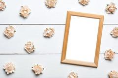 Le cadre vide de photo avec des roses au-dessus de blanc a peint le fond Images libres de droits