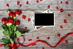 Le cadre vide de photo et les roses rouges fleurit avec des pétales Image stock