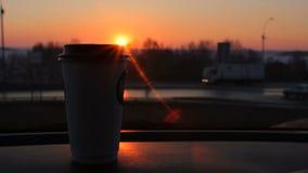 Le café à aller tasse se tenant sur le coucher du soleil de panneau de voiture et route urbaine trafiquent le fond banque de vidéos