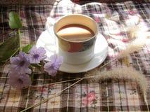 Le café avec les fleurs pourpres et l'herbe sèche fleurit sur la table avec le soleil de matin Image libre de droits
