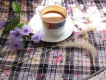 Le café avec les fleurs pourpres et l'herbe sèche fleurit sur la table avec le soleil de matin Images libres de droits