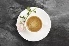 Le café d'expresso dans une tasse blanche et un rose s'est levé sur un backgro foncé Images libres de droits