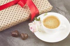 Le café d'expresso dans une tasse blanche, un rose s'est levé, un cadeau avec un t rouge Images libres de droits