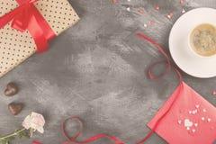 Le café d'expresso dans une tasse blanche, un rose s'est levé, un cadeau avec un t rouge Photographie stock