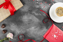 Le café d'expresso dans une tasse blanche, un rose s'est levé, un cadeau avec un t rouge Photographie stock libre de droits