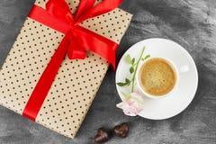 Le café d'expresso dans une tasse blanche, un rose s'est levé, un cadeau avec un t rouge Image stock