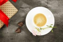Le café d'expresso dans une tasse blanche, un rose s'est levé, un cadeau avec un t rouge Image libre de droits