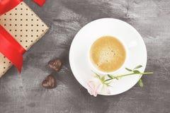 Le café d'expresso dans une tasse blanche, un rose s'est levé, un cadeau avec un t rouge Photo libre de droits