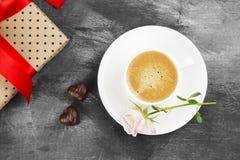 Le café d'expresso dans une tasse blanche, un rose s'est levé, un cadeau avec un t rouge Photos libres de droits