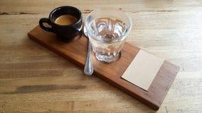 Le café d'expresso a tiré dans la tasse noire du plat en bois avec le cuppi Photos libres de droits