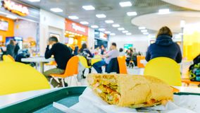 le café de Temps-faute, sandwich mordu se trouve sur la table dans la perspective des visiteurs troubles de consommation image libre de droits