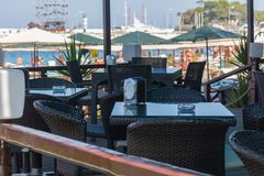 Le café de touristes sur le bord de la mer avec une vue sur des bateaux dans le port et des paumes le long de la côte, mer, Turqu Photo stock