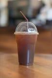 Le café glacé d'Americano emportent dedans le verre en plastique de tasse sur l'OE Image stock
