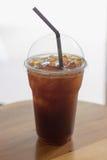 Le café glacé d'Americano emportent dedans le verre en plastique de tasse sur l'OE Photo libre de droits