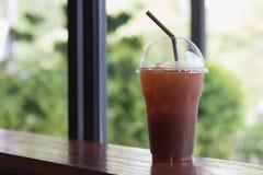 Le café glacé d'Americano emportent dedans le verre en plastique de tasse sur l'OE Photographie stock