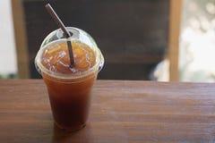 Le café glacé d'Americano emportent dedans le verre en plastique de tasse sur l'OE Images libres de droits