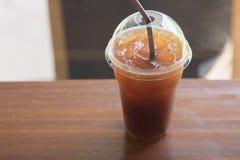 Le café glacé d'Americano emportent dedans le verre en plastique de tasse sur l'OE Images stock