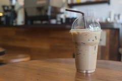 Le café glacé emportent dedans le verre en plastique de tasse sur le Tableau I en bois Images stock