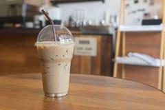 Le café glacé emportent dedans le verre en plastique de tasse sur le Tableau I en bois Photos libres de droits