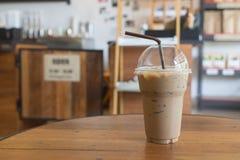 Le café glacé emportent dedans le verre en plastique de tasse sur le Tableau I en bois Photo libre de droits
