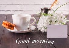 Le café, les macarons sur une soucoupe et un bouquet des fleurs avec une carte l'inscription est bonjour Image libre de droits