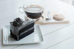 Le café noir d'americano chaud et le morceau d'A de charbon de bois durcissent sur la table en bois blanche Images stock