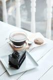 Le café noir d'americano chaud et le morceau d'A de charbon de bois durcissent sur la table en bois blanche Photos libres de droits