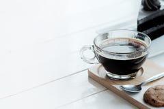 Le café noir d'americano chaud et le morceau d'A de charbon de bois durcissent sur la table en bois blanche Photographie stock libre de droits