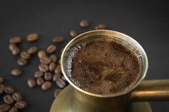 Le café noir dans le vieux cezve de cuivre et les grains de café sur le noir ont brouillé le plat d'ardoise comme fond avec l'esp Photos libres de droits