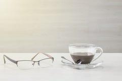 Le café noir de plan rapproché dans la tasse transparente de café et de lunettes sur le bureau et le mur en bois brouillés a donn Images stock