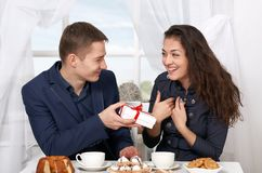 Le café potable de couples heureux et l'amusement de avoir, homme donnent les cadeaux très drôles - concept d'amour et de vacance Image libre de droits