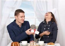 Le café potable de couples heureux et l'amusement de avoir, homme donnent les cadeaux très drôles - concept d'amour et de vacance Photographie stock