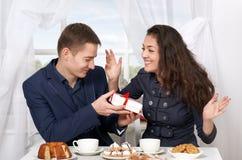 Le café potable de couples heureux et l'amusement de avoir, homme donnent les cadeaux très drôles - concept d'amour et de vacance Images libres de droits