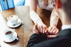Le café potable de jeunes mariés dans un café à la table en bois ronde doucement se tenant mains du ` s Photographie stock