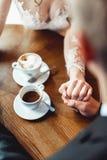 Le café potable de jeunes mariés dans un café à la table en bois ronde doucement se tenant mains du ` s Images libres de droits