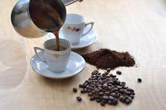 Le café s'est renversé du cezve pour mettre en forme de tasse photos stock