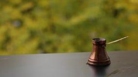 Le café savoureux chaud dans la tasse rouge a brassé dans un pot traditionnel de café turc, table de café dehors clips vidéos