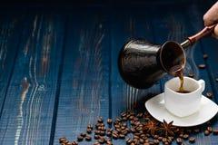 Le café se renverse dans une tasse sur une table en bois bleue avec des grains de café photo libre de droits
