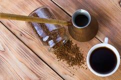 Le caf? se tient ? c?t? d'une tasse blanche remplie du caf? chaud parmi les grains de caf? dispers?s, table, vue sup?rieure, hori photo libre de droits