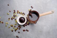 Le café turc avec les grains de café et le cardamome a dispersé sur un fond de vintage Photo stock