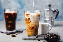 Le café de glace dans un verre grand avec de la crème s'est renversé plus d'et des grains de café Photos stock