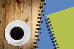 Le café et le croquis blanc réservent sur le bois ta Photographie stock libre de droits