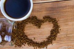 Le caf? se tient ? c?t? d'une tasse blanche remplie du caf? chaud parmi les grains de caf? dispers?s, table, vue sup?rieure, hori photos libres de droits