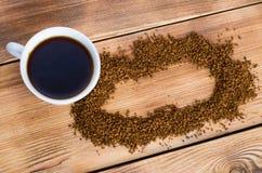 Le caf? se tient ? c?t? d'une tasse blanche remplie du caf? chaud parmi les grains de caf? dispers?s, table, vue sup?rieure, hori image libre de droits