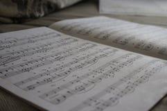 Le cahier de musique ouvert pour jouer un piano Image stock