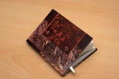 Le cahier fermé avec le crayon lecteur à l'intérieur Photographie stock