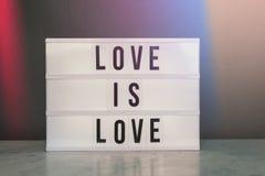 Le caisson lumineux avec amour de ` est ` et arc-en-ciel d'amour Photo stock