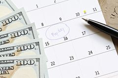 Le calendrier avec le cercle de marqueur bleu dans le jour de paie de mot et les dollars américains encaissent l'argent pour rapp photo stock