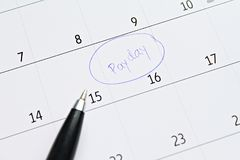 Le calendrier avec le cercle de marqueur bleu dans le jour de paie de mot pour rappellent images stock